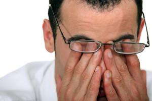 Mann mit Brille reibt die verklebten Augen